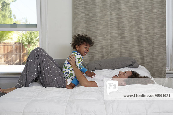 Male toddler sitting on top of mother on bed
