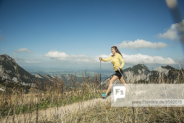 Austria  Tyrol  Tannheim Valley  young woman nordic walking in mountains