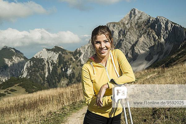 Österreich  Tirol  Tannheimer Tal  lächelnde junge Frau mit Nordic Walking Stöcken im Gebirge