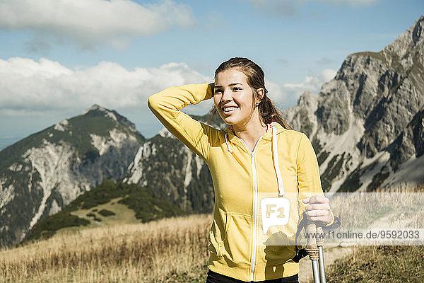 Österreich,  Tirol,  Tannheimer Tal,  lächelnde junge Frau mit Nordic Walking Stöcken im Gebirge