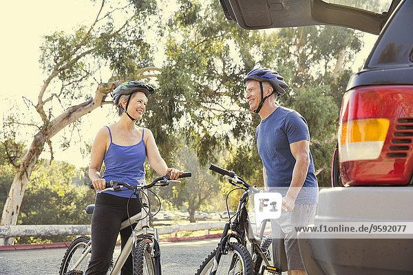 Ein reifes Radfahrerpaar beim Plaudern im Park