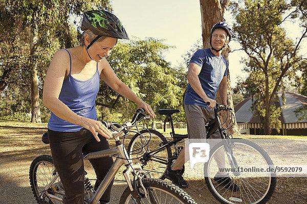 Reife Paare plaudern auf Fahrrädern im Park