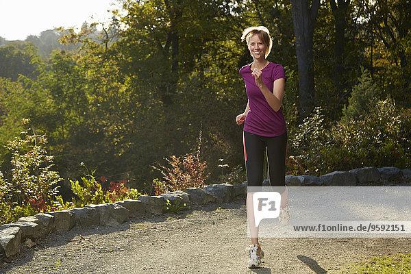 Mittlere erwachsene Frau beim Laufen im Park