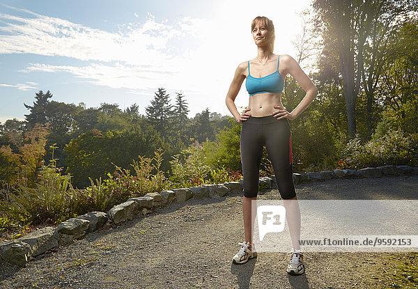 Porträt der Läuferin mit den Händen auf den Hüften im Park