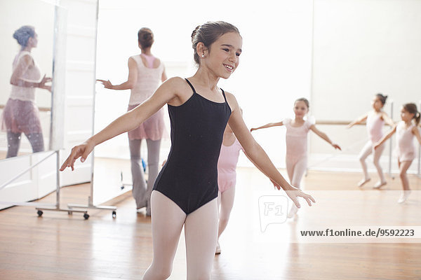 Teacher and girls practicing ballet dancing in ballet school