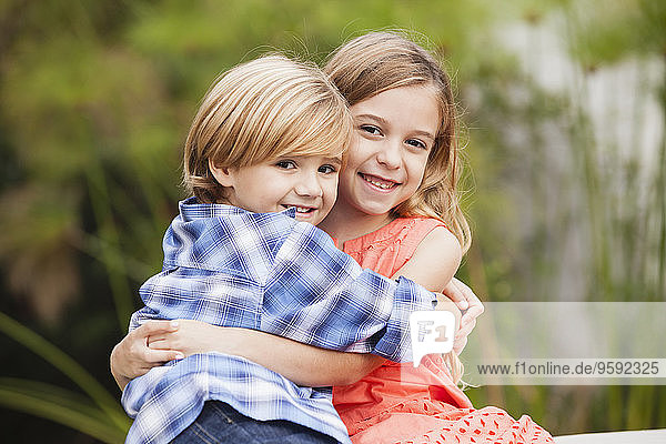 Mädchen und Jungen umarmen sich im Freien