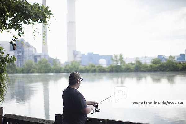 Mann beim Fischen gegenüber Detroit Edison Power Station  Fluss Raisin  Monroe  Michigan  USA
