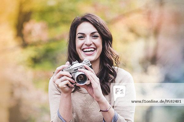 Porträt einer lächelnden jungen Frau mit Spiegelreflexkamera im Herbstwald Porträt einer lächelnden jungen Frau mit Spiegelreflexkamera im Herbstwald