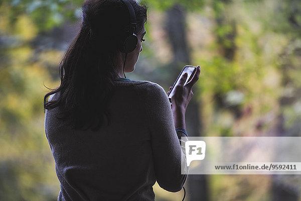 Junge Frau im Wald schaut auf das Smartphone und hört Kopfhörer. Junge Frau im Wald schaut auf das Smartphone und hört Kopfhörer.