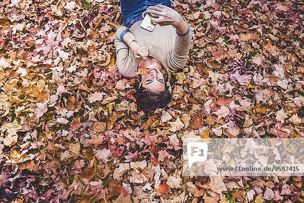 Overhead-Ansicht einer jungen Frau  die auf Herbstblättern liegt und Smartphone Selfie nimmt.