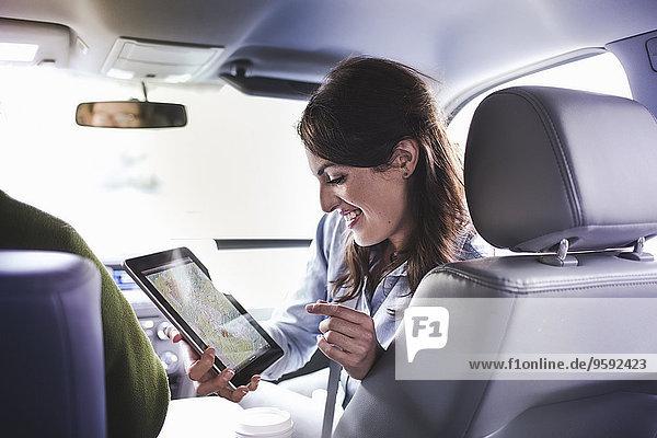 Über-Schulter-Ansicht der jungen Frau auf dem Vordersitz mit digitaler Tablettkarte Über-Schulter-Ansicht der jungen Frau auf dem Vordersitz mit digitaler Tablettkarte