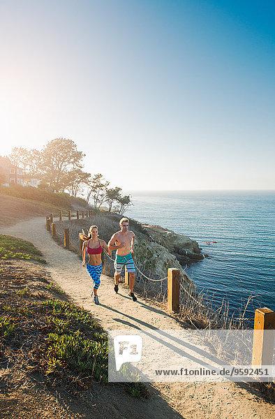 Mittlerer erwachsener Mann und junge Frau beim Joggen auf dem Seeweg