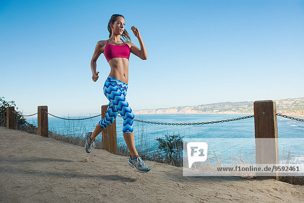Young woman running on path by sea