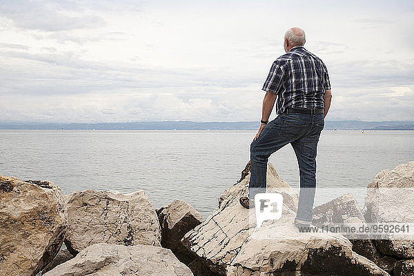 Slowenien  Piran  Mann auf Felsen am Wasser mit Blick auf den Horizont