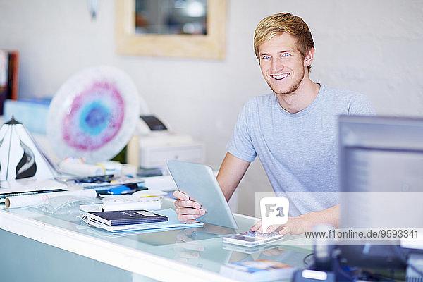 Lächelnder junger Mann an der Ladentheke