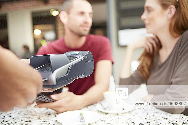 Service mit Kreditkartenleser in einem Straßencafé