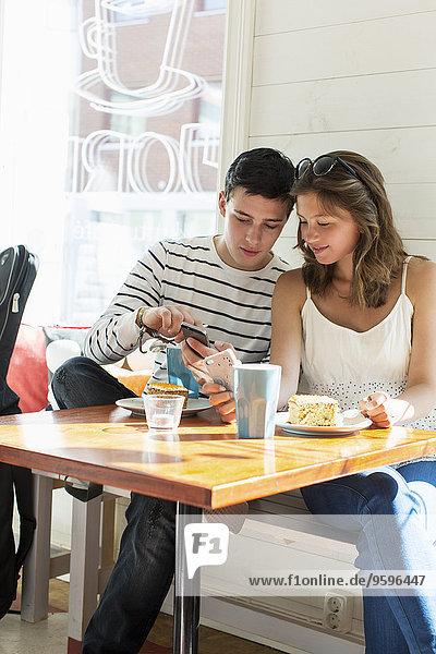 Pärchen mit Mobiltelefonen beim Sitzen am Restauranttisch