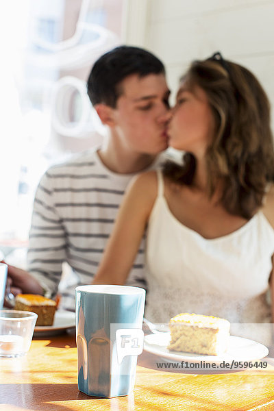 Couple kissing while sitting at restaurant table