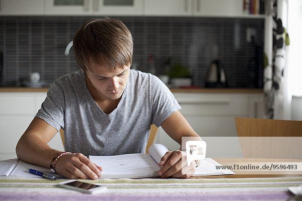 Junger Mann liest Buch bei Tisch im Haus