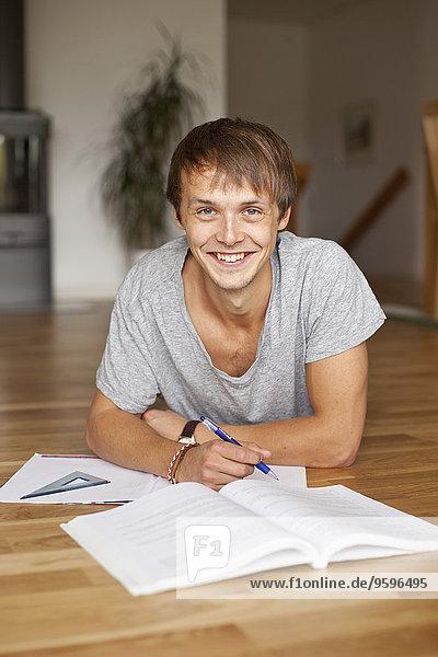 Porträt eines glücklichen jungen Mannes  der zu Hause auf dem Boden liegt.