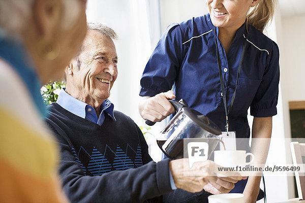 Mittelteil einer glücklichen Frau  die dem älteren Mann im Pflegeheim schwarzen Kaffee serviert.