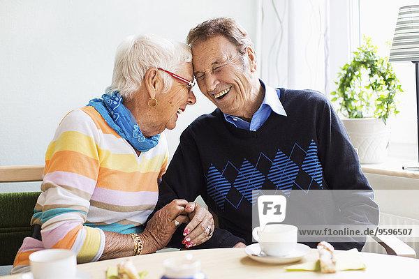 Liebevolles Seniorenpaar lacht im Pflegeheim