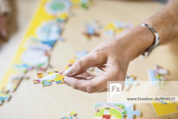 Abgeschnittenes Bild einer älteren Frau  die ein Puzzleteil am Tisch im Pflegeheim hält.