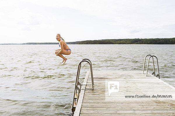 Seitenansicht der aufgeregten Frau  die in den See springt.