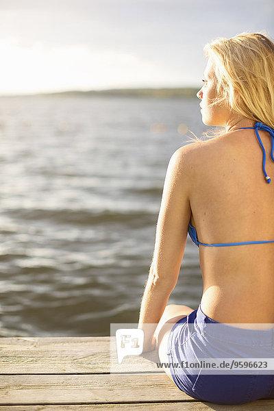 Rückansicht der jungen Frau im Bikini-Top auf der Uferpromenade am See