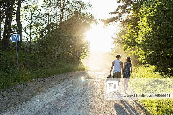 Durchgehende Rückansicht des Paares auf dem unbefestigten Weg