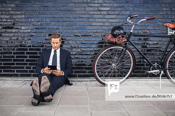 Volle Länge des Geschäftsmannes  der mit dem Fahrrad auf dem Bürgersteig sitzt.
