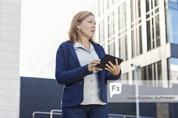 Geschäftsfrau schaut weg  während sie ein digitales Tablett außerhalb des Bürogebäudes benutzt.