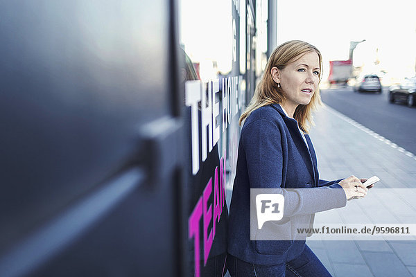Businesswoman looking away while using mobile phone on sidewalk