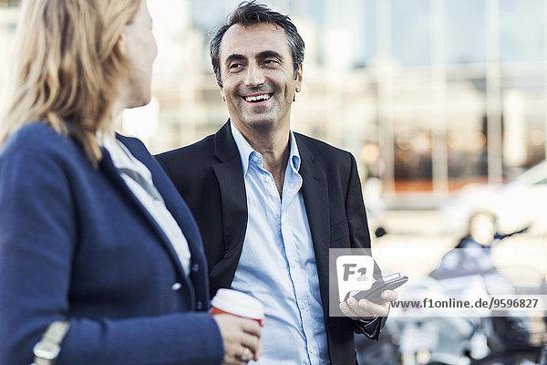 Glücklicher Geschäftsmann im Gespräch mit einer Kollegin im Freien