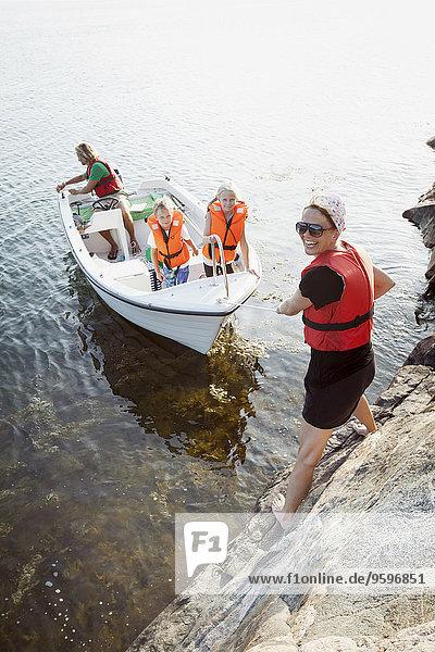 Porträt einer glücklichen Frau  die eine Familie im Boot zieht.