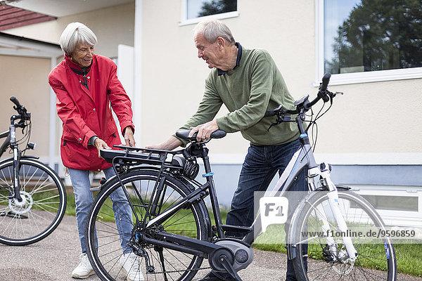 Seniorenpaar beim Einsetzen der Batterie in den Rücksitz des Elektrofahrrades außerhalb des Hauses