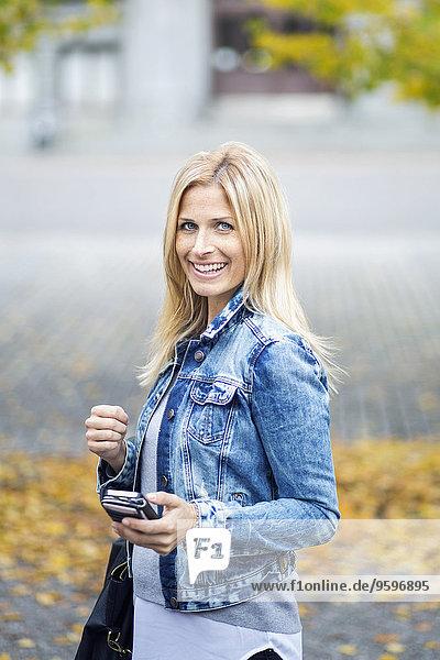 Seitenansicht Porträt einer lächelnden mittleren erwachsenen Frau mit Smartphone im Park