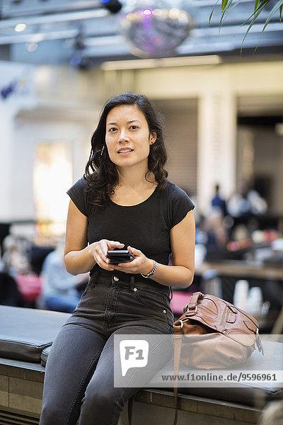 Porträt einer Frau mit Handy im Restaurant