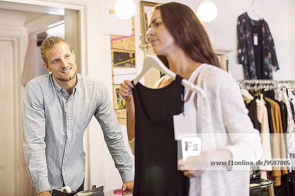 Männlicher Besitzer schaut sich die Kundin an  die ein Abendkleid in der Boutique ausprobiert.
