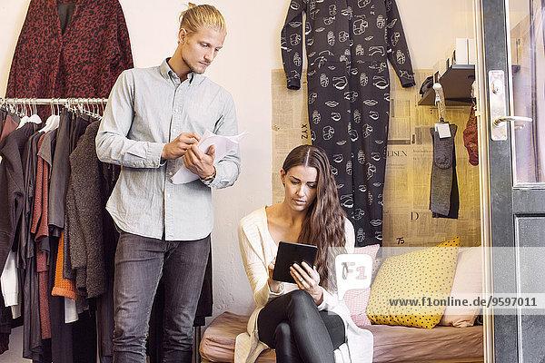 Mann sucht Frau mit digitalem Tablett im Bekleidungsgeschäft