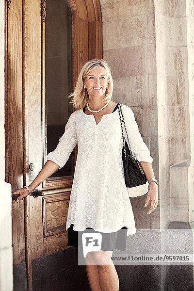 Portrait of happy woman opening door