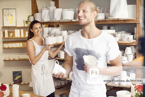 Glückliche Arbeiter  die in der Geschirrwerkstatt handwerkliche Produkte arrangieren.