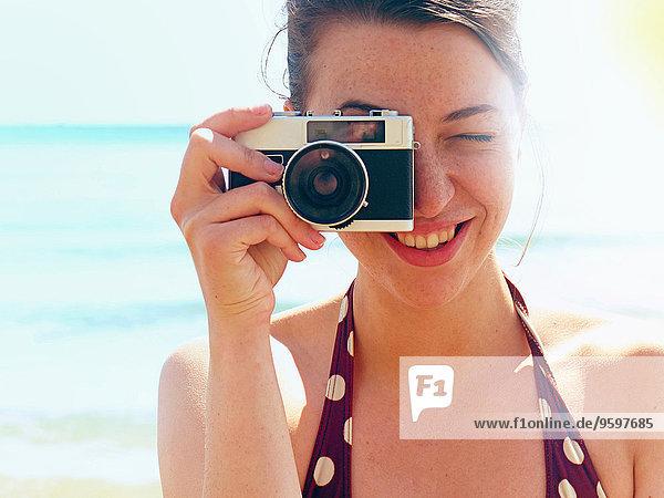 Junge Frau mit Kamera am Strand