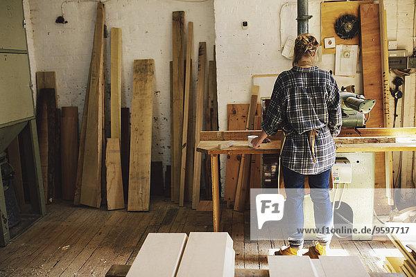 Junge Handwerkerin an der Werkbank in der Pfeifenorgel-Werkstatt
