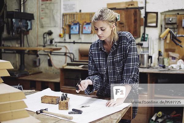 Junge Handwerkerin beim Prüfen von Bauteilen auf der Werkbank in der Pfeifenorgel-Werkstatt