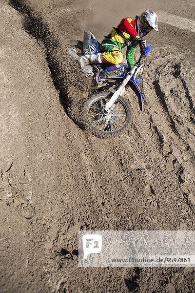 Junger männlicher Motocross-Fahrer  der den Schlammberg hinunterfährt