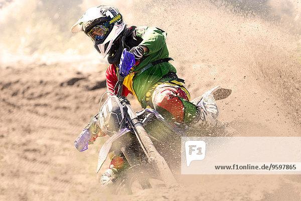 Junge männliche Motocross-Fahrer  die sich in die Schlammbahn lehnen.