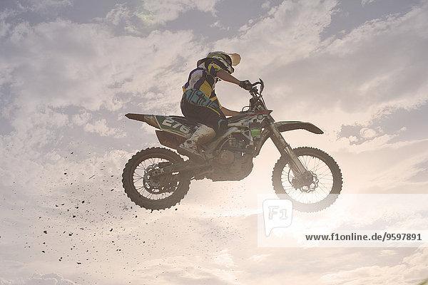 Silhouettierter junger  männlicher Motocross-Rennfahrer  der in der Luft springt.