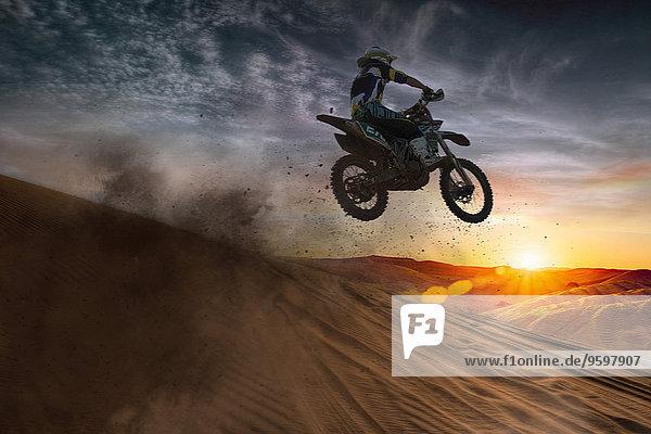 Junge männliche Motocrosser springen bei Sonnenuntergang in der Luft