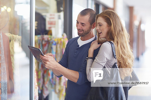 Couple window shopping  holding digital tablet